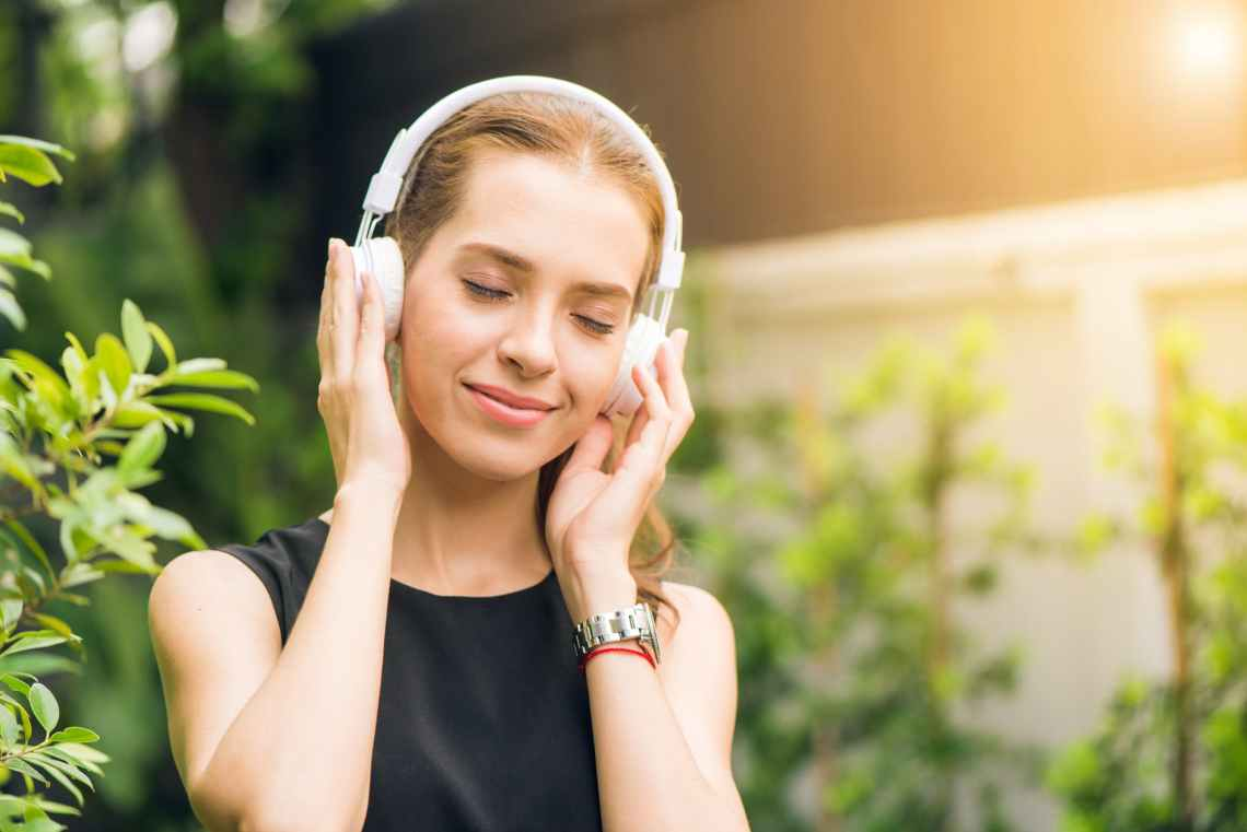 woman wearing black sleeveless dress holding white headphone at daytime